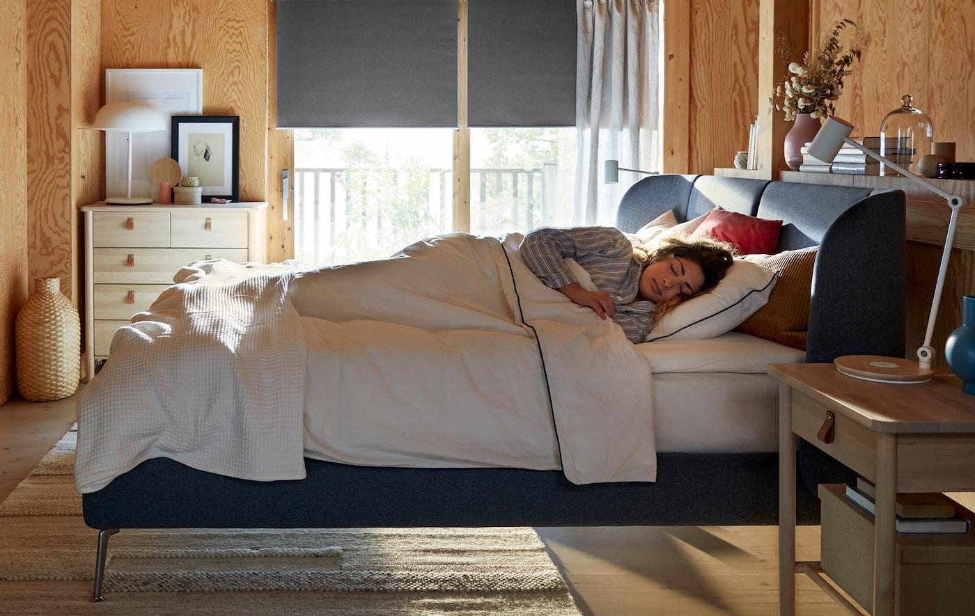 O femeie doarme întinsă într-un pat albastru TUFJORD, în timp ce lumina pătrunde prin fereastra din spatele ei în cameră.