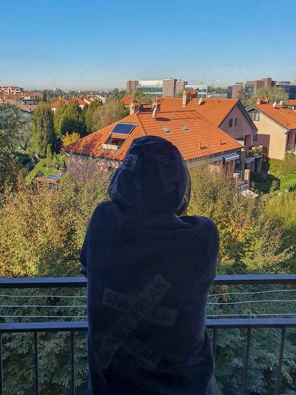 O femeie îmbrăcată cu un hanorac negru stă pe un balcon, privind la cartierul ei.
