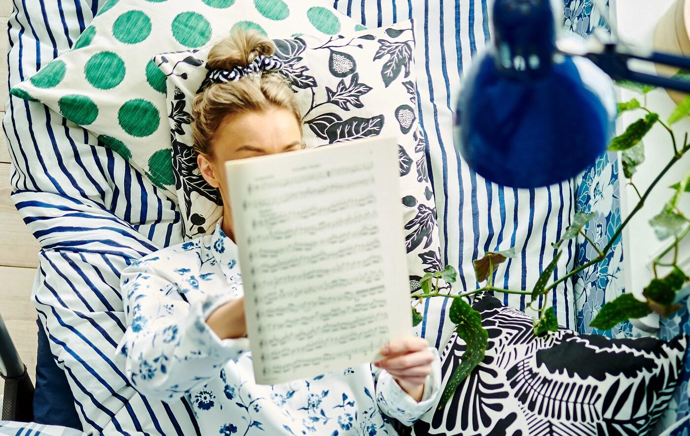 O femeie stă întinsă într-un un pat cu perne, lenjerie de pat și tapet cu modele diferite în jurul ei citind note muzicale.