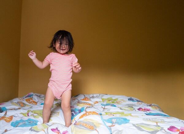 O fetiță cu părul brunet, care îi acoperă fața, sare pe un pat. Se distrează.