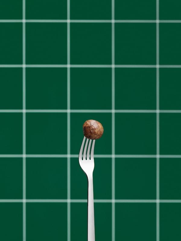 O furculiță din oțel inoxidabil ținută în poziție verticală în care este înfiptă o chifteluță vegetală. Perete cu faianță verde în fundal.
