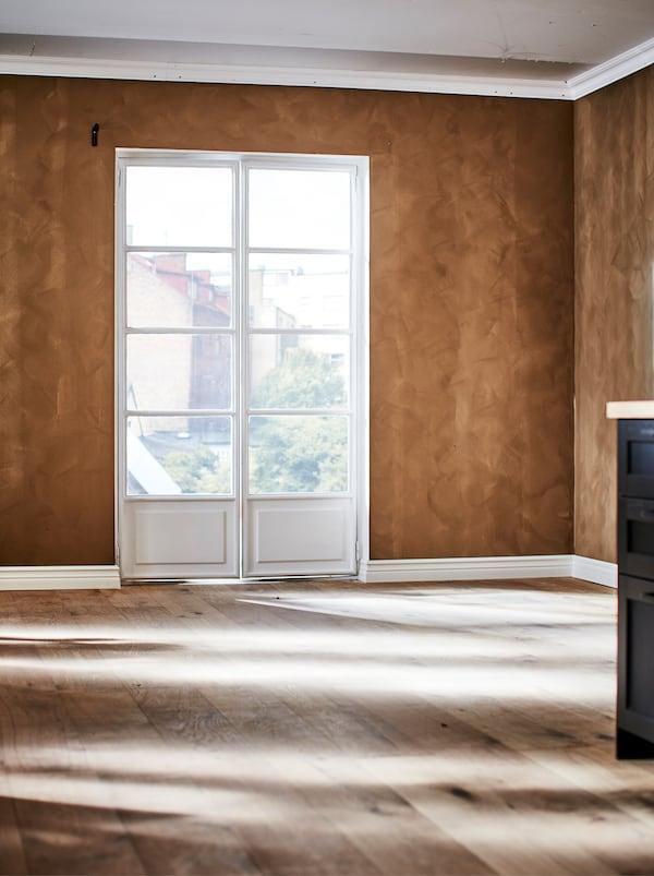 O încăpere goală cu ferestre în stil franțuzesc, pardoseală din lemn și perete zugrăvit într-un ton de maroniu bogat, cu finisaj mat catifelat.