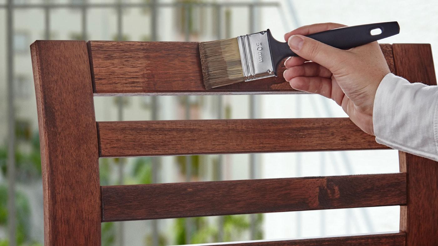 O mână care ține o pensulă cu care acoperă cu baiț spătarul unui scaun din lemn de exterior.