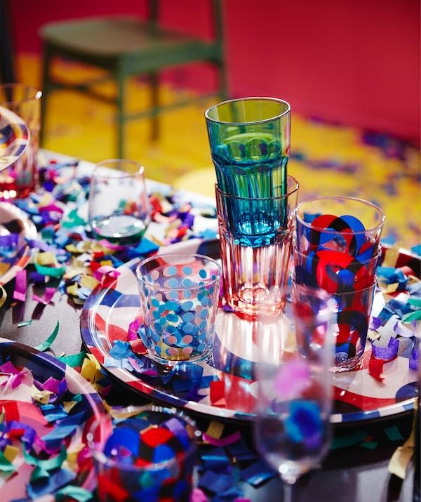 O masă de petrecere cu confetti și o tavă cu pahare FRAMKALLA  și POKAL cu roșu și albastru.