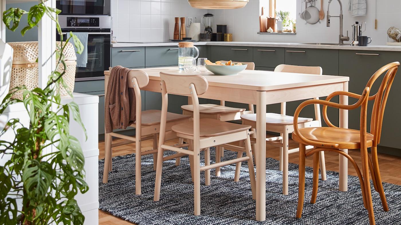 O masă din lemn de mesteacăn și patru scaune din familia de produse RÖNNINGE, plus un scaun IKEA din anii 60.