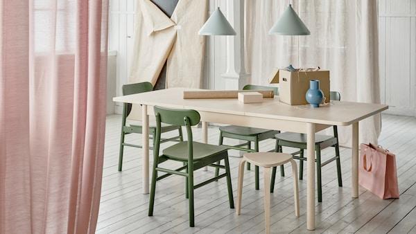 O masă extensibilă RÖNNINGE, cu extensia în uz, este așezată într-o cameră de zi unde se află și alte obiecte în curs de împachetare.