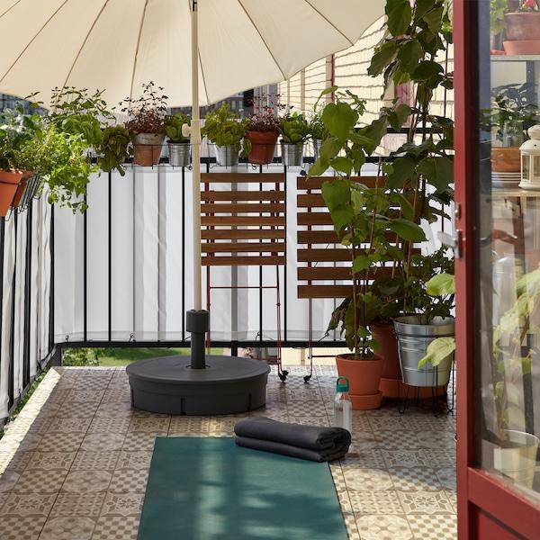 O masă și un scaun pliate și așezate într-o parte, pentru a face spațiu unui covor de yoga întins pe podeaua balconului.