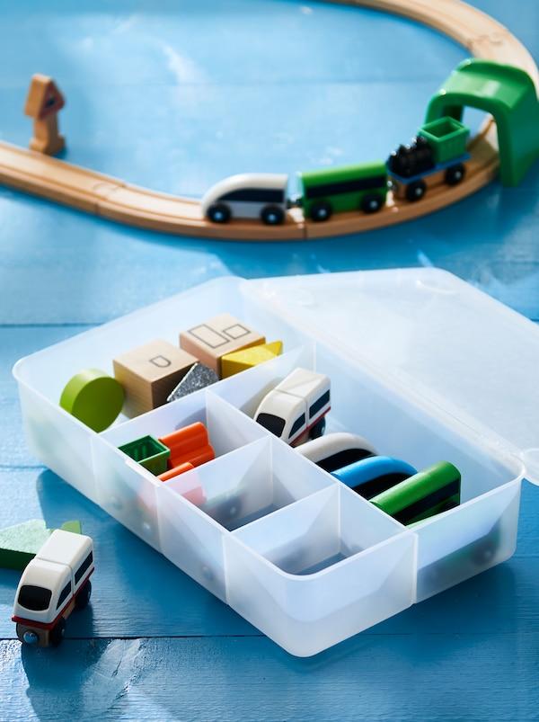 O parte a unei șine din lemn, un tren de jucărie plasat pe șină. Lângă ele se află cutie GLIS plină cu accesorii sortate.