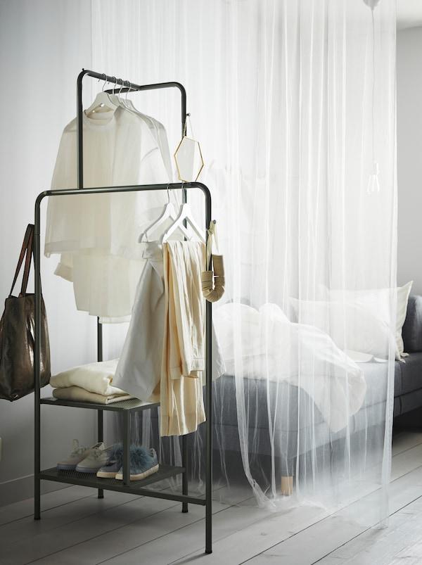O perdea albă transparentă separă o canapea de un suport de umerașe NIKKEBY gri/verde cu încălțăminte, haine și accesorii.
