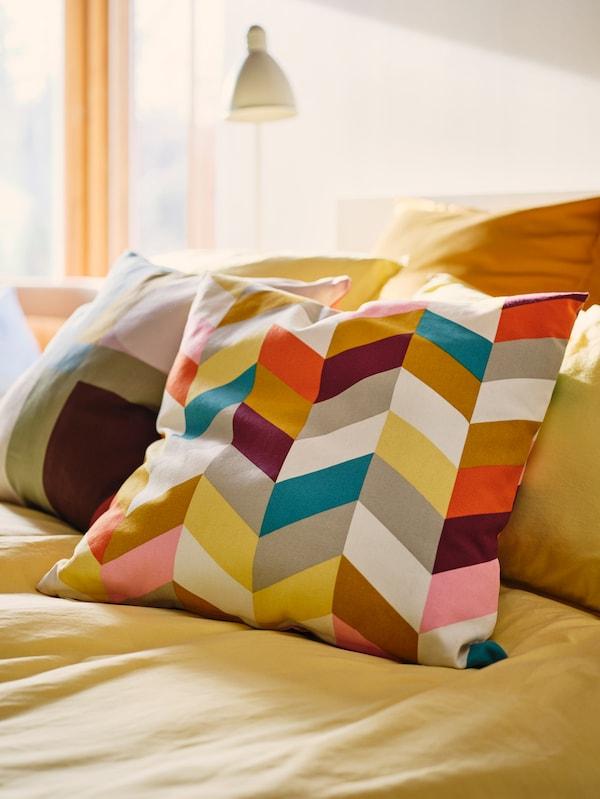 O pereche de perne îmbrăcate în fețe de pernă HANNELISE și STENMÄTARE sunt așezate pe o cuvertură galben intens într-un dormitor.