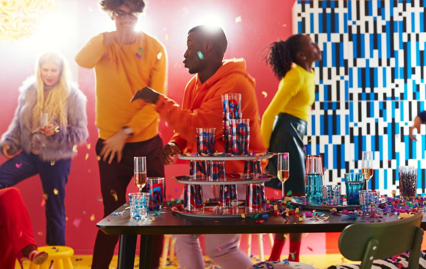 O petrecere plină de culoare cu diferite tipuri de pahare, precum paharele FRAMKALLA  cu modele șerpuitoare și îndrăznețe în albastru și roșu.