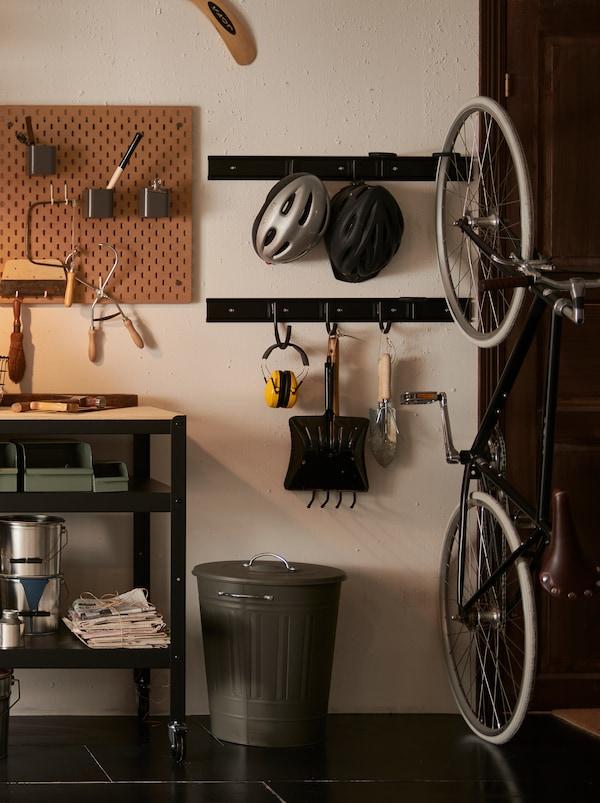 O secțiune a unui garaj cu un coș metalic KNODD gri cu un capac și unelte de grădinărit agățate de cârlige din metal negru pe perete.