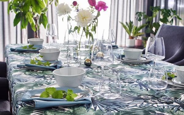 O tecido IKEA TORGERD ten un estampado con palmeiras. Confecciona un mantel tropical. Combínalo con floreiros de cristal transparente e pratos de cerámica branca KRUSTAD.