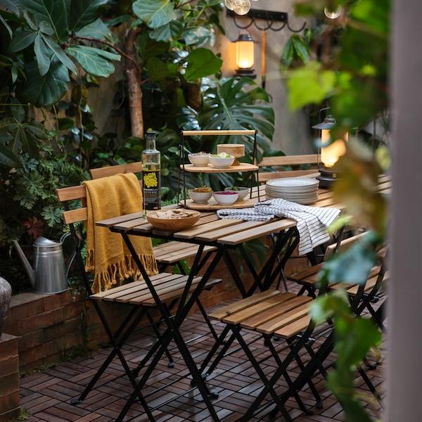 O terasă cu o mulțime de plante verzi, scaune și mese de exterior în combinația lemn de salcâm/negru, o pătură galbenă și o tavă de servire din bambus.