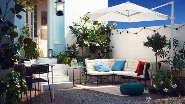 O terasă în aer liber, cu o canapea modulară cu perne albe, o umbrelă albă, un pouf albastru-verde și o mulțime de plante.