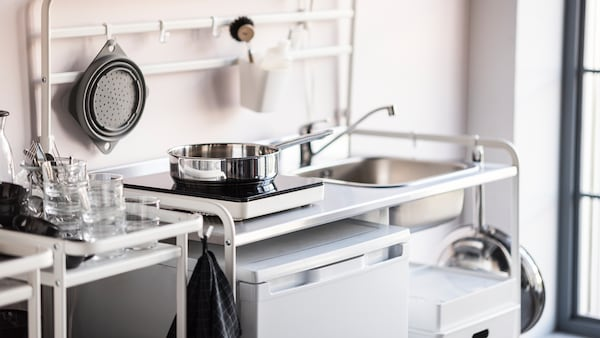 O tigaie din inox care stă pe o plită portabilă cu inducție TILLREDA, într-o mini-bucătărie SUNNERSTA.