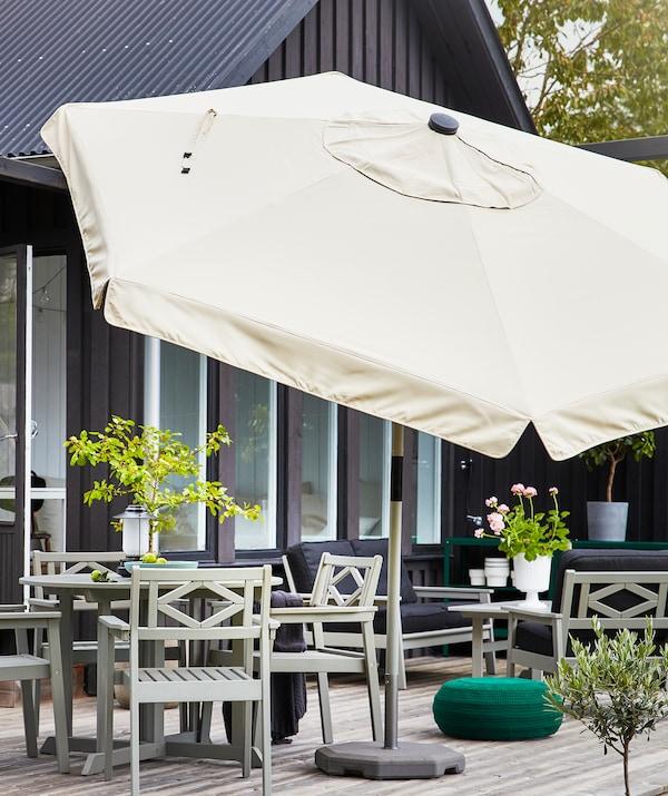 O umbrelă mare bej pe o terasă cu mobilier de exterior gri și plante.