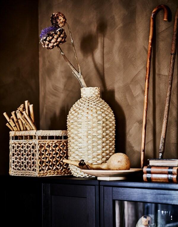 O vază decorativă KAFFEBÖNA realizată din detalii din bambus cu detalii deco din materiale organice se află pe partea superioară a unui corp HAVSTA maro închis.