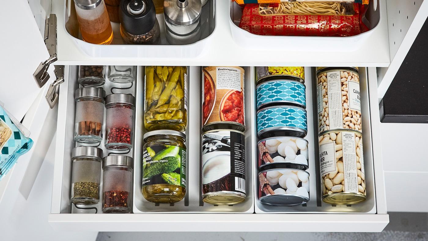 O vedere de aproape a unui sertar deschis cu conserve, cutii și condimente organizate cu ajutorul separatoarelor VARIERA.