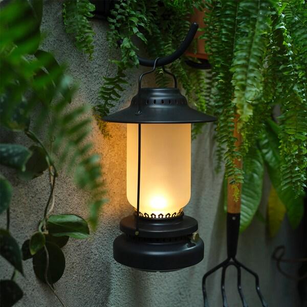 O veioză cu LED neagră care arată ca un felinar este agățată de un cârlig montat pe perete și emană o lumină caldă și blândă.