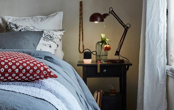 O veioză pe o masă lângă un pat luminează o vază de sticlă și un ceas cu alarmă într-un dormitor confortabil.