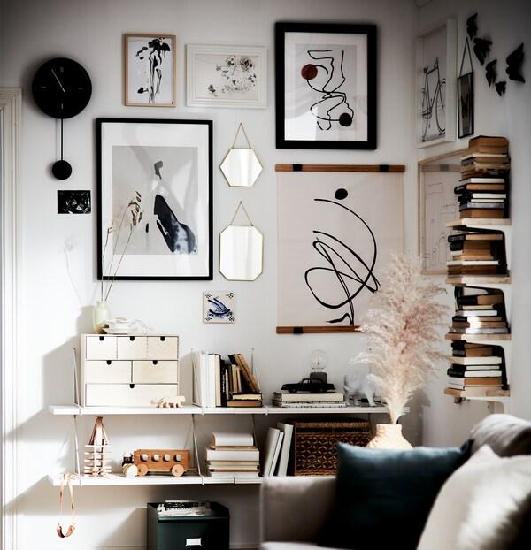O zonă de cameră de zi cu cărți de anticariat, accente în materiale naturale și un perete cu lucrări de artă în culori alb, negru și ovăz.