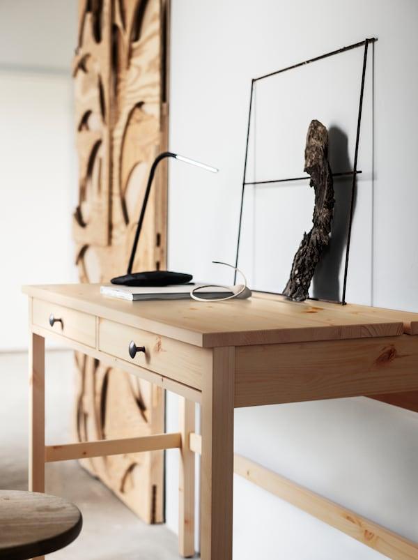 Obiecte realizate din lemn ușor, netratat, așezate de-a lungul unui perete într-o cameră albă, printre care un birou HEMNES cu sertare.