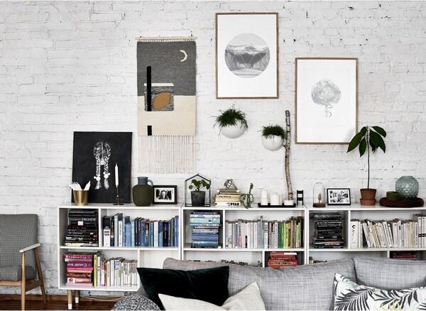 Obra d'art a una paret de totxo blanca amb llibres i plantes en una prestatgeria baixa.