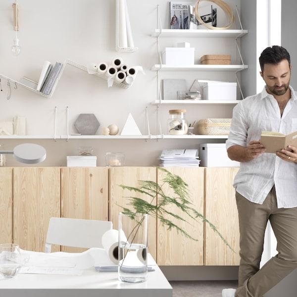 Obrázek muže, který stojí a čte si knihu v domácí kanceláři ze světlého dřeva a v bílé barvě.