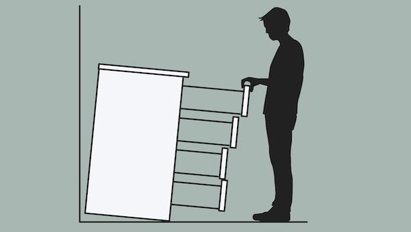 Obrázok skrinky so zásuvkami, ktorá nie je pripevnená k stene a prevracia sa na muža, ktorý vytiahol všetky zásuvky.