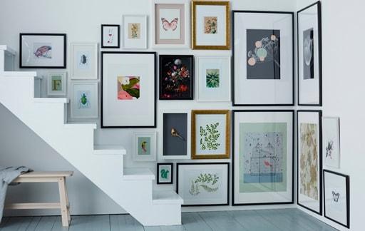 obrazy w ramkach różnej wielkości zawieszone w narożniku i nad schodami