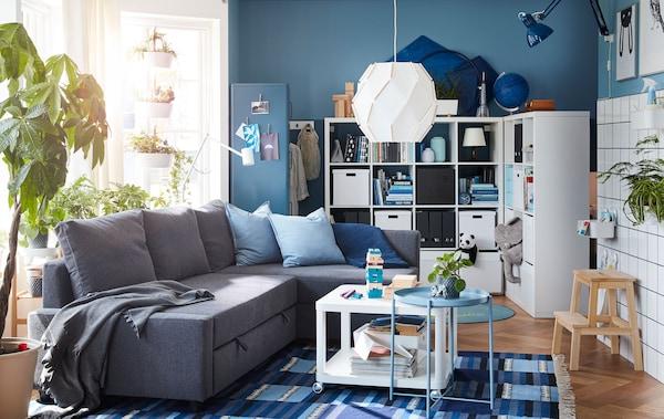 Obývací pokoj, rohová pohovka, policové díly, velká květina před velkým oknem
