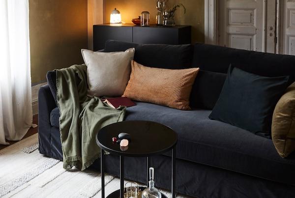 Obývací pokoj s pohovkou, polštáři, plédem, kobercem, stolkem, příborníkem s lampou, vázami, a ratanovým křeslem.