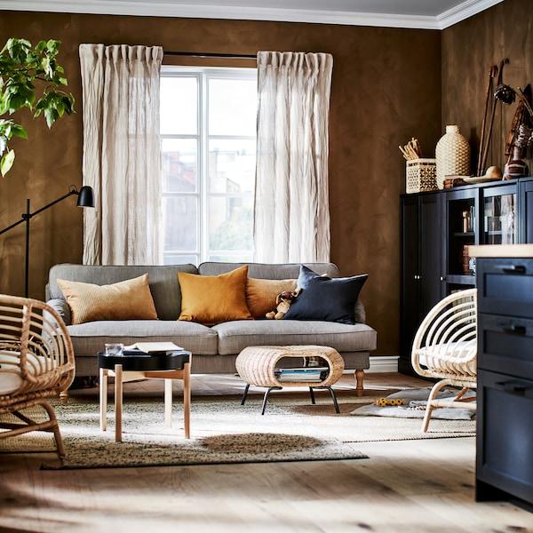 Obývací pokoj s šedo-béžovou pohovkou, dvěma jutovými koberci, dvěma křesly,  béžovými lněnými závěsy a tmavými skříněmi