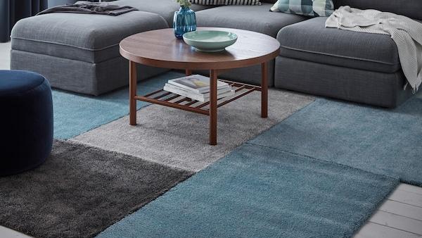 Obývací pokoj s šedou pohovkou, kulatým stolkem a řadou koberců v modré a šedé barvě