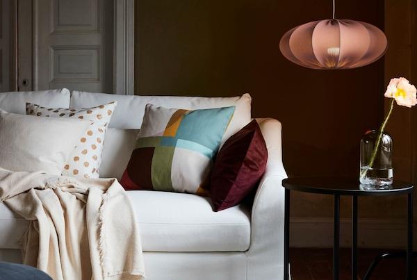 Obývací pokoj s tmavou pohovkou, světlým kobercem, polštáři a plédem, stojací lampou a příborníkem s dekorativními předměty.