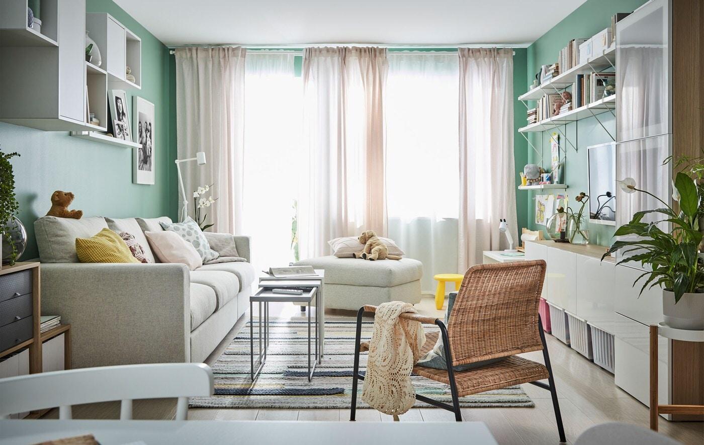 Obývací pokoj se záclonami, velkým oknem, pohovkou a skříňkami
