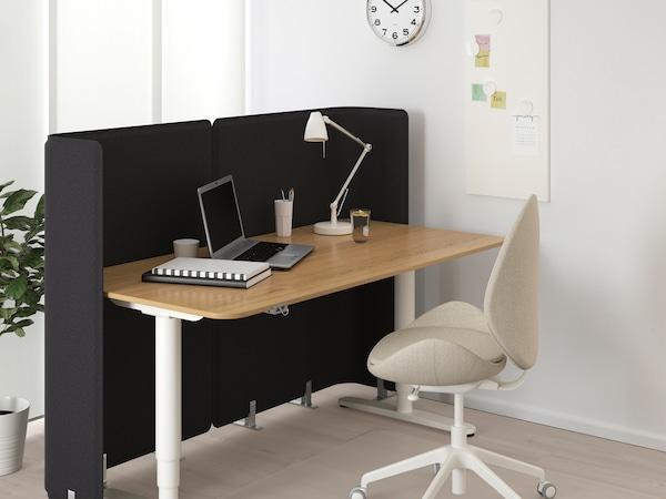 Obývacia izba s pracovnou stoličkou, stolom a tmavým panelom na predelenie miestnosti upevneným k stolu.