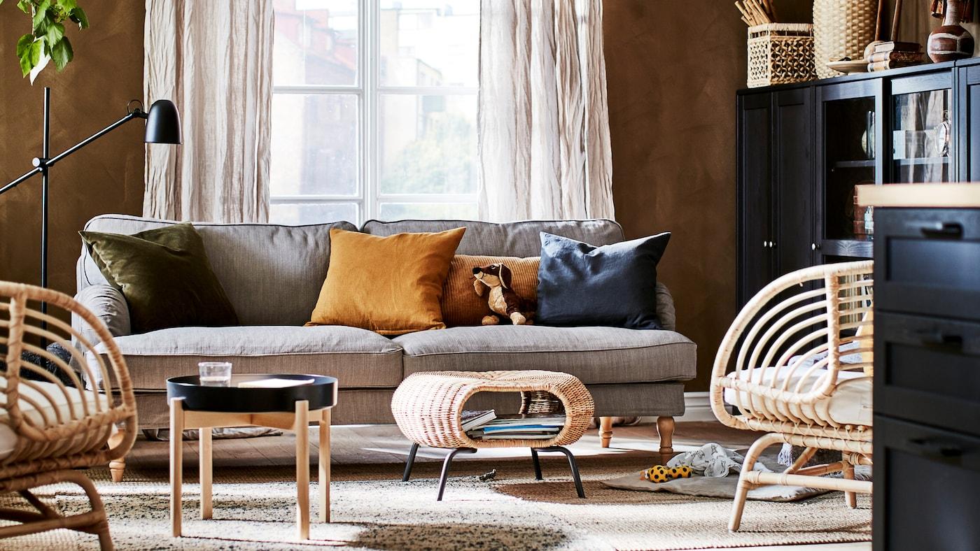 Obývacia izba v zemitých farbách s dekoráciami, úložnými priestormi, sedením, príručným stolíkom, podnožkou a rastlinou.