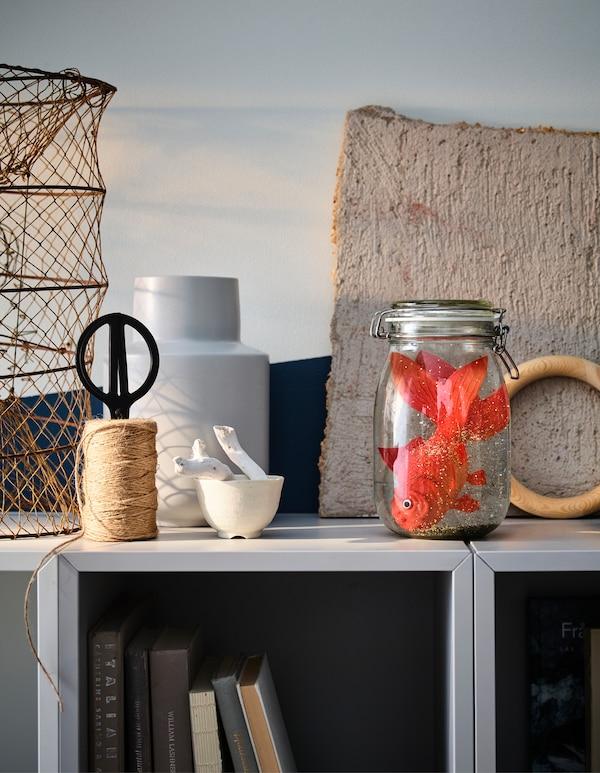 """Očajnički tražiš neke nove ideje za ukrašavanje dnevne sobe nadolazećih blagdana? Izradi """"Uradi sam/a"""" snježnu kuglu! Robna kuća IKEA nudi razne staklene spremnike i staklenke koje možeš upotrijebiti, primjerice KORKEN staklenku + poklopac."""