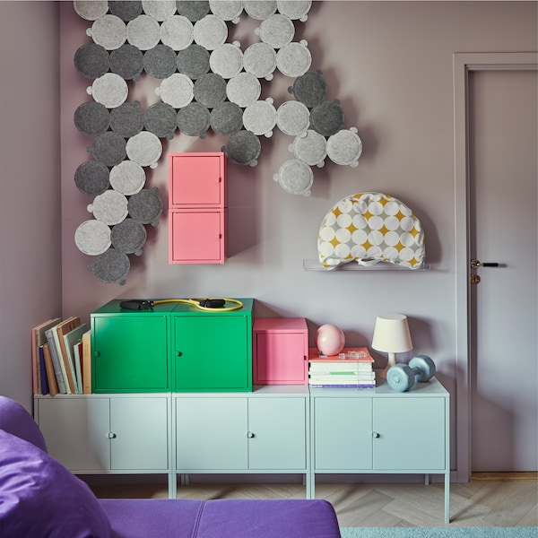 ODDLAUG sound absorbing panels in gray, on the wall of a small living space with storage cabinets and boxes, and a bed sofa.