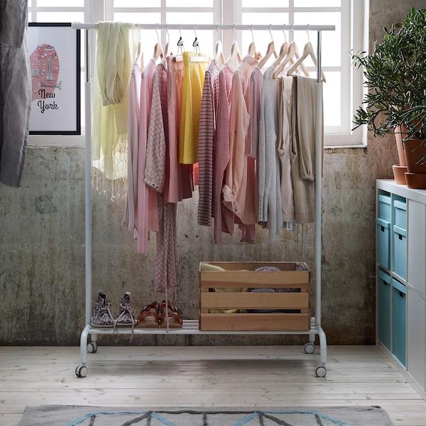 Odeća pastelnih boja visi s bele RIGGA šine za odeću u sobi punoj svetlosti.