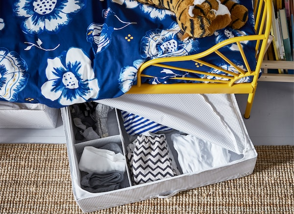 Odeća u otvorenoj kutiji za odlaganje ispod dečjeg kreveta sa žutim okvirom i plavom cvetnom krevetninom.