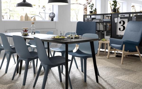 ODGER كراسي سوداء من ايكيا على شكل أوعية وطاولة طعام LISABO سوداء مستطيلة الشكل في قاعة طعام مفتوحة.