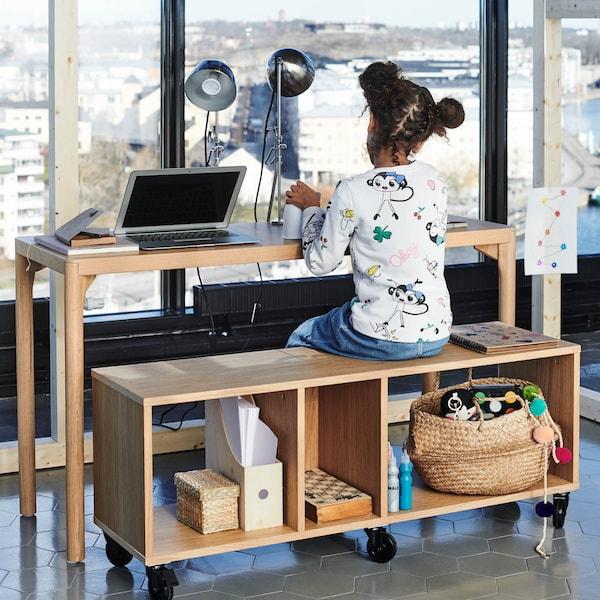 Odkládací stolík RÅRAROR a lavice s kolieskami, na ktorej sedí malé dievčatko.
