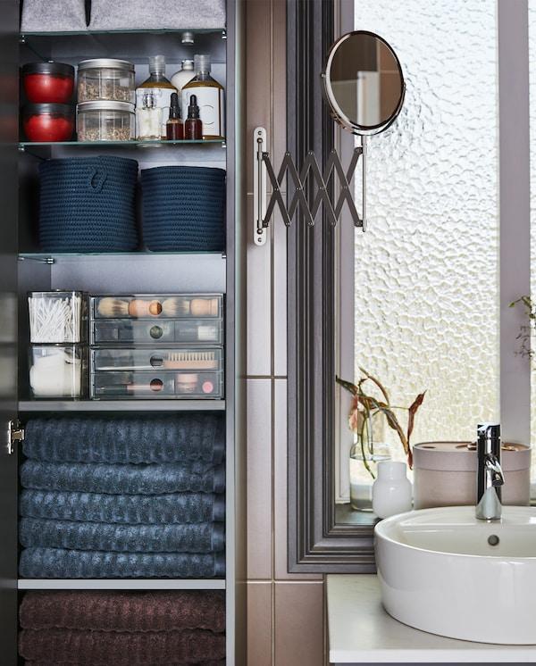 Öppet högskåp med mörkgrå handdukar, transparenta lådor, burkar och blå korgar på hyllorna samt en spegel på sidan.