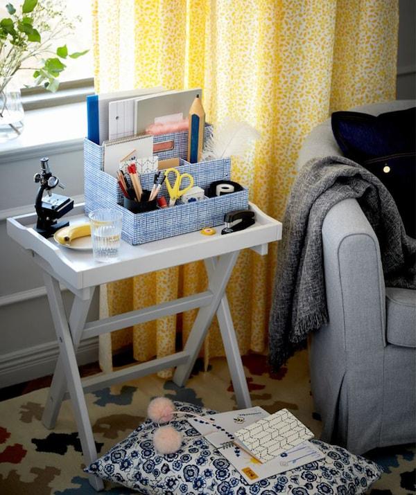 Összecsukható asztalka egy fotel mellett.