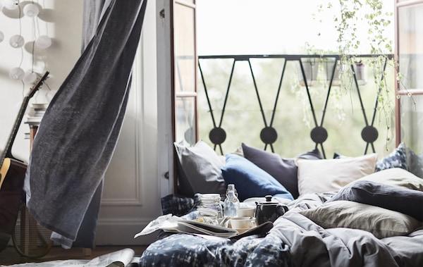 Offene Balkontüren mit Kissen und Bettwäsche auf einer Matratze, die auf dem Boden liegt.