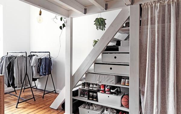 Offene Kleiderstangen und Fächer unter einer Treppe.