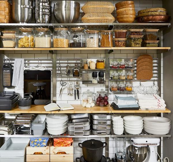 Offene Küchenregale aus Holz, Küchengeräte wie das TILLREDA tragbare Induktionsfeld und ein KUNGSFORS Tablethalter, an dem Kräuter befestigt sind.